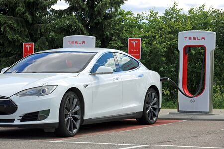 supercharger: PAIMIO, FINLAND - JUNE 4, 2016: White Tesla Model S electric car is being charged at Tesla Supercharger station. Charging the battery from 10 to 80 percent takes about 40 minutes.