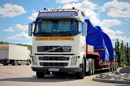 oversize load: PAIMIO, FINLAND - JUNE 12, 2016: Volvo FH truck with two industrial objects on trailer as oversize load iis parked on a truck stop in South of Finland.