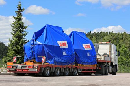 PAIMIO, FINLANDIA - 12 DE JUNIO, 2016: camión Volvo FH está listo para transportar dos objetos industriales en el remolque como carga de gran tamaño en el sur de Finlandia. Editorial