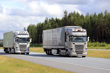 overtaking: SALO, FINLAND - JUNE 19, 2016: Scania R490 cargo trucks overtakes another Scania truck R410 on motorway in on a clear day of summer in South of Finland.