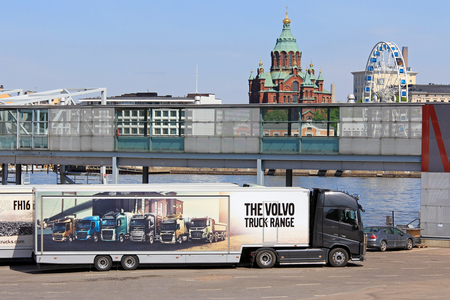 HELSINKI, FINLAND - MAY 24, 2016: Volvo FH16 750 semi parked at Olympic terminal, Helsinki, shows the Volvo truck range pictured on trailer, with Uspenski Cathedral and SkyWheel Helsinki on the background.