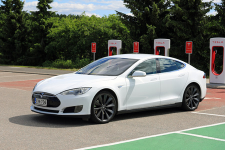 supercharger: PAIMIO, FINLAND - JUNE 4, 2016: White Tesla Model S electric car leaves Tesla Supercharger station. Charging the battery from 10 to 80 percent takes about 40 minutes.