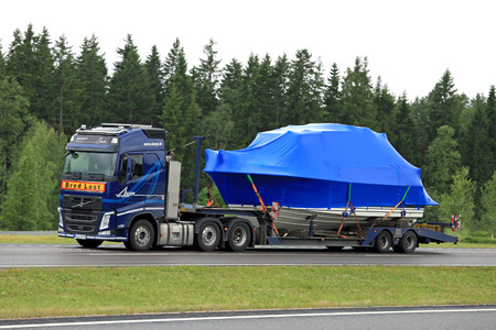 exceptional: PAIMIO, FINLAND - JUNE 23, 2016: Blue Volvo FH semi truck hauls a boat as exceptional load along freeway. Abnormal transport permit is required, if any dimension of the load exceeds the free dimension limits.