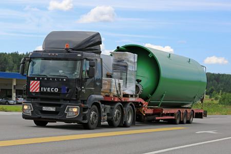 oversize load: SALO, FINLAND - JULY 8, 2016: Black Iveco Stralis 420 semi truck transports a large industrial object on flat trailer along highway at summer.
