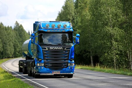 flanked: TENHOLA, FINLAND - JULY 30, 2016: Blue Scania R580 tank truck on rural highway flanked by green forest at summer. Editorial