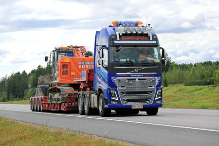 tracked: PAIMIO, FINLAND - JULY 31, 2016: Volvo FH16 600 hauls Hitachi tracked excavator on Noteboom trailer along freeway in South of Finland.