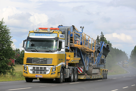 ee: SALO, FINLAND - JULY 30, 2016: Yellow Volvo FH of EE Mantyla transports Fintec 570 Screen  on lowboy trailer along highway. Another heavy transport follows.