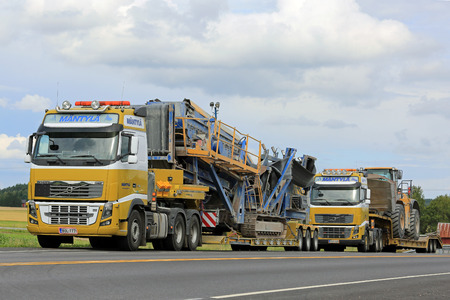 oversize load: SALO, FINLAND - JULY 30, 2016: Two Yellow Volvo FH16 semi trucks  of Mantyla E & E in heavy equipment haul stop for a moment by road in South of Finland. The trucks transport screener and Cat wheel loader on drop deck trailer. Editorial