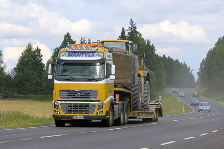 ee: SALO, FINLAND - JULY 30, 2016: Yellow Volvo FH16 semi of Mantyla E&E transports Caterpillar 980H wheel loader on drop deck trailer on rural highway at summer. The Cat 980H has an operating weight of 30159 kg. Editorial