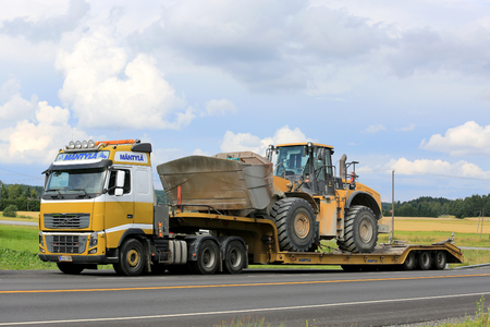 SALO, FINLAND - JULY 30, 2016: Yellow Volvo FH16 semi of Mantyla E & E in heavy equipment haul stops for a moment by road in South of Finland. The truck transports Cat 980H wheel loader on drop deck trailer. Editorial