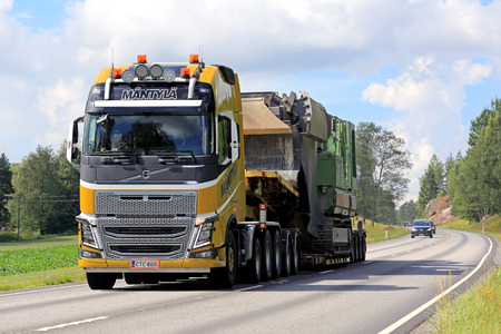 oversize load: TENHOLA, FINLAND - JULY 30, 2016: Yellow Volvo FH16 750 semi of Mantyla E & E transports construction equipment as oversize load along rural highway in South of Finland. Editorial
