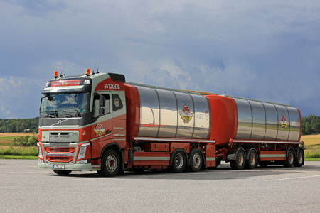 hauler: SALO, FINLAND - AUGUST 7, 2016: Colorful Volvo FH 500 tank truck of Johns Rasmussen, Denmark parked on the asphalt yard of a scenic truck stop in South of Finland.