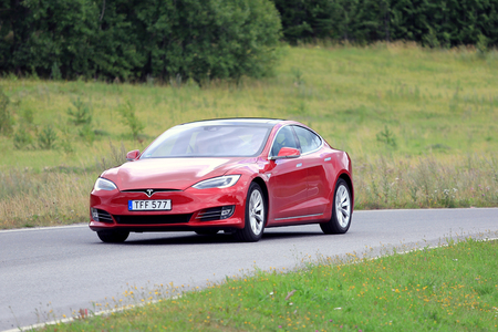 new look: PAIMIO, FINLAND - JULY 31, 2016: Tesla Model S luxury sedan with the new look on rural road in South of Finland. Tesla updates also the exterior of the Model S in April 2016. Editorial