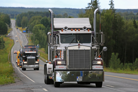 convoy: IKAALINEN, FINLAND - AUGUST 11, 2016: Classic Kenworth W900B semi moves along scenic highway as part of the truck convoy to the annual trucking event Power Truck Show 2016.