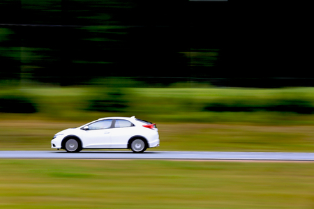 panning: Small white car in high speed on the motorway, panning technique, copy space right.