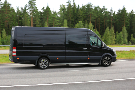 PAIMIO, FINLAND - AUGUST 5, 2016: Black Mercedes-Benz Sprinter van moves along motorway at high speed in South of Finland. Panning effect.