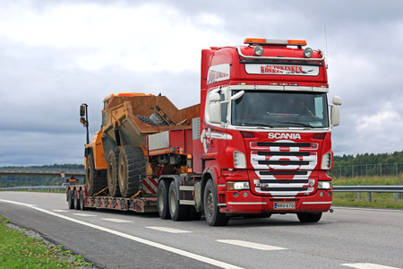 v8: SALO, FINLAND - AUGUST 26, 2016: Red Scania R620 V8 hauls mining equipment on lowboy trailer along freeway in South of Finland on an overcast day.