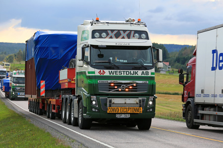 oversize load: JAMSA, FINLAND - SEPTEMBER 1, 2016: Volvo FH semi truck of Westdijk AB hauls wide load in convoy among busy traffic in Central Finland. Editorial