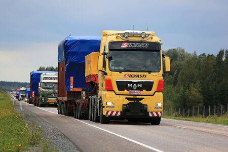 v8: ORIVESI, FINLAND - SEPTEMBER 1, 2016: Yellow MAN V8 semi truck hauls wide load in convoy of four exceptional road transports of industrial objects.
