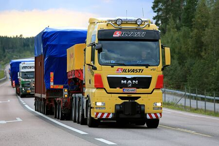 oversize load: ORIVESI, FINLAND - SEPTEMBER 1, 2016: Yellow MAN V8 semi truck hauls wide load in convoy of four exceptional road transports of industrial objects.