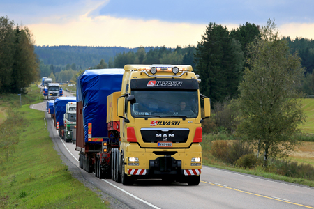 oversize load: JAMSA, FINLAND - SEPTEMBER 1, 2016: Yellow MAN V8 semi truck hauls wide load first in convoy of four exceptional road transports of industrial objects. Editorial