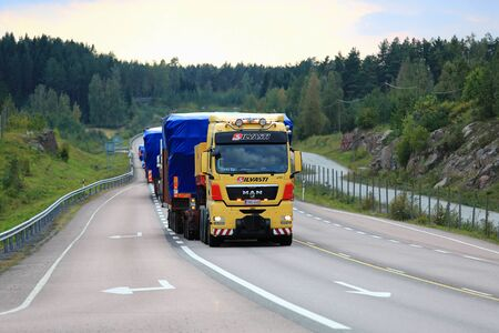 oversize load: ORIVESI, FINLAND - SEPTEMBER 1, 2016: Yellow MAN V8 semi truck of Silvasti leads the convoy of wide load road transports in the evening along  scenic highway in Central Finland.