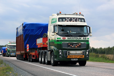 oversize load: JAMSA, FINLAND - SEPTEMBER 1, 2016: Two Volvo FH semi trucks of Westdijk AB haul wide load in convoy of four exceptional road transports in Central Finland. Editorial