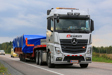 benz: ORIVESI, FINLAND - SEPTEMBER 1, 2016: Silver Mercedes-Benz Actros 3351 semi truck hauls wide load accompanied by an escort vehicle in Central Finland.