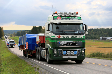 oversize load: JAMSA, FINLAND - SEPTEMBER 1, 2016: Volvo FH semi truck of Westdijk AB hauls oversized industrial object in convoy with other wide load road transports among traffic in Central Finland.
