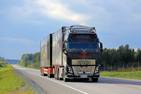 hauler: ORIVESI, FINLAND - SEPTEMBER 1, 2016: The specatular show truck Volvo FH16 Ace of Spades moving along road in Central Finland under dark overcast sky.