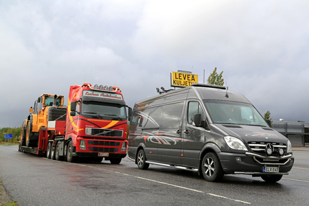 oversize: FORSSA, FINLAND - SEPTEMBER 4, 2016: Mercedes-Benz Sprinter pilot vehicle and Volvo FH semi truck transporting wheel loader as oversize load parked on a truck stop asphalt yard on a rainy day. Editorial