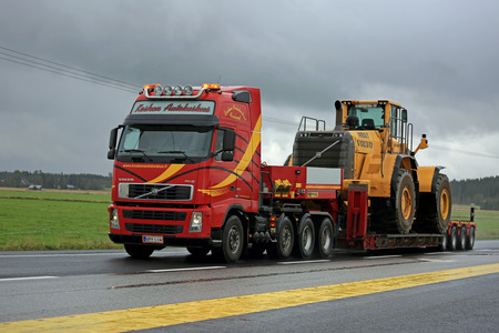 4 wheel: FORSSA, FINLAND - SEPTEMBER 4, 2016: Red Volvo FH12 semi truck transports Volvo wheel loader as oversize load along highway on a rainy day.