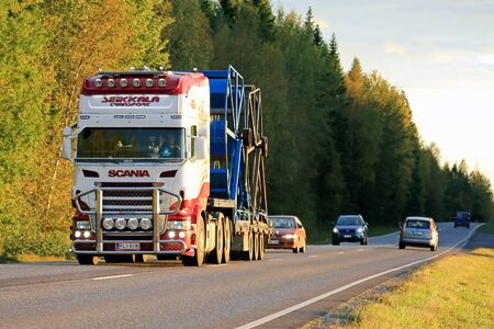commercial tree service: SALO, FINLAND - SEPTEMBER 9, 2016: Customized Scania semi of Seikkala Transport hauls industrial object on lowboy trailer on autumn road at sunset time.