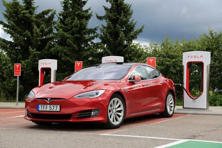 PAIMIO, FINLANDIA - 31 de julio, 2016: sedán de lujo Tesla Model S con el nuevo diseño en la parte exterior del vehículo se carga en la estación de Supercharger Tesla. Foto de archivo - 62874914