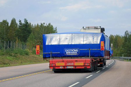 oversize: ORIVESI, FINLAND - SEPTEMBER 1, 2016: Rear view of a semi truck which transports an oversize load on lowboy trailer along highway in Central Finland. Editorial