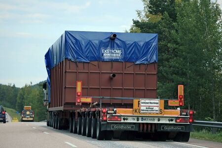 oversize: ORIVESI, FINLAND - SEPTEMBER 1, 2016: Oversize load transport truck with two pilot cars leading the way, rear view, seen from the car passing the vehicle.