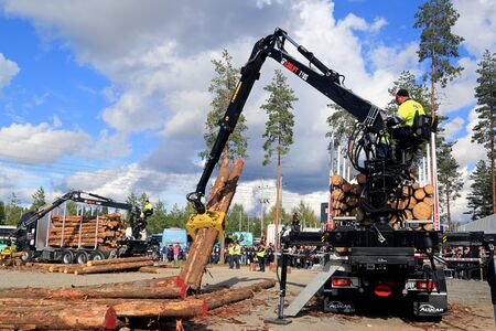 finalists: JAMSA, FINLAND - SEPTEMBER 2, 2016: Two finalists compete in the Finnish Championships in Log Loading 2016, held at FinnMETKO 2016.