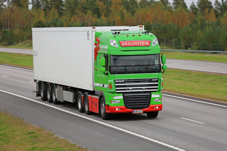 reefer: PAIMIO, FINLAND - SEPTEMBER 23, 2016: Lime green DAF XF reefer truck of Braunstein moving along freeway in South of Finland.
