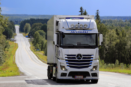 daimler: IKAALINEN, FINLAND - AUGUST 11, 2016: White Mercedes-Benz Actros refrigerated transport truck of Jarvimaki moves uphill on scenic road in South of Finland.