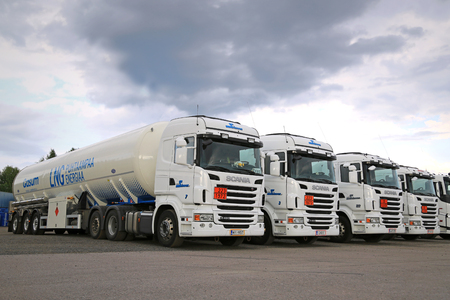 RAJAMAKI, FINLAND - JULY 2, 2016: Fleet of white Scania R480 semi tank trucks with ADR plates for Liquefied natural gas, LNG transport parked on asphalt yard.