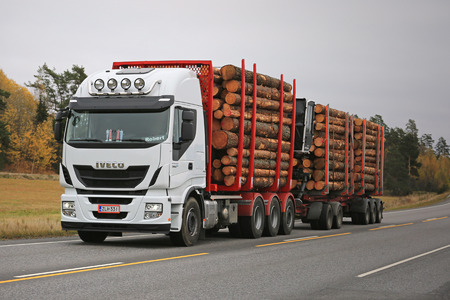 KAARINA, FINLAND - OCTOBER 14, 2016: New white Iveco Stralis 560 logging truck hauls a full load of timber along autumnal highway in South of Finland.