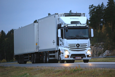 PAIMIO, FINLAND - OCTOBER 14, 2016: White Mercedes-Benz Actros 2545 refrigerator truck of H. Mikkola transports goods along motorway late in the evening. Editoriali