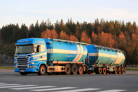 tree service business: FORSSA, FINLAND - OCTOBER 17, 2015: Blue and white Scania R580  double tanker of E.Laurila Oy parked on truck stop in evening light with trees in autumn colors on the background. Editorial