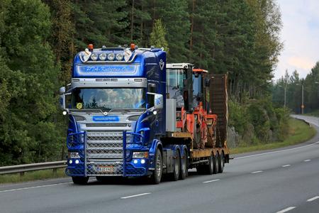 ORIVESI, FINLAND - SEPTEMBER 1, 2016: Customized blue and silver Scania  semi V8 of PTA-Kuljetus hauls roadworks equipment along rural road in Finland.