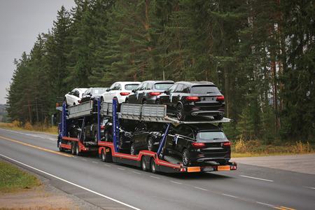 Salo, Finlandia - el 22 de DE OCTUBRE DE, 2016: Mercedes-Benz Actros lances del transportador de coches nuevos coches del MB a lo largo de la carretera de otoño en el sur de Finlandia.