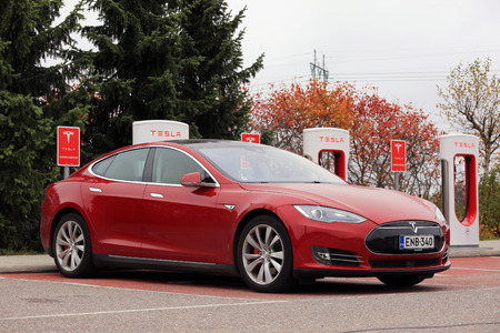 updated: PAIMIO, FINLAND - OCTOBER 14, 2016: Red Tesla Model S luxury sedan is being charged at Tesla Supercharger Station.