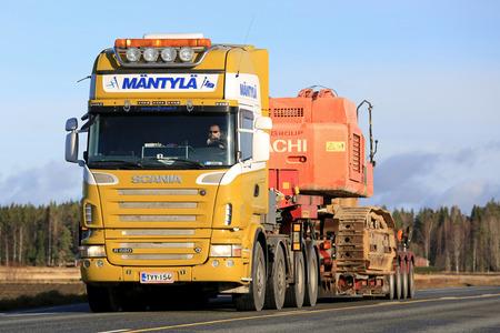 oversize: JOKIOINEN, FINLAND - OCTOBER 29, 2016: Scania R620 Semi truck of Mantyla hauls large Hitachi tracked excavator on lowboy trailer along highway as oversize load. Editorial
