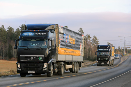 highway 6: KAARINA, FINLAND - NOVEMBER 6, 2016: Two black Volvo FH semi trucks transport Mobil Delvac heavy duty diesel engine oil along highway on early winter afternoon.