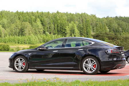 PAIMIO, FINLAND - JULY 17, 2016: Black Tesla Model S electric car charging battery on Tesla Supercharger in South of Finland, side view. Editorial