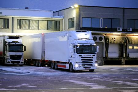 살로, 핀란드 -2010 년 11 월 27 일 : 겨울 저녁 폭설 warehause에서 언로드 준비 큰 흰색 냉장 트레일러 트럭.